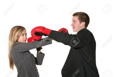 761459-Two-business-people-with-boxing-gloves-on-in-the-middle-of-conflict-Stock-Photo